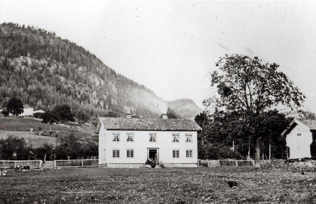 Gården Lundevall (Lundevold), Kviteseid. Hvit hovedbygning med loft. Inngjerdet område bak huset.