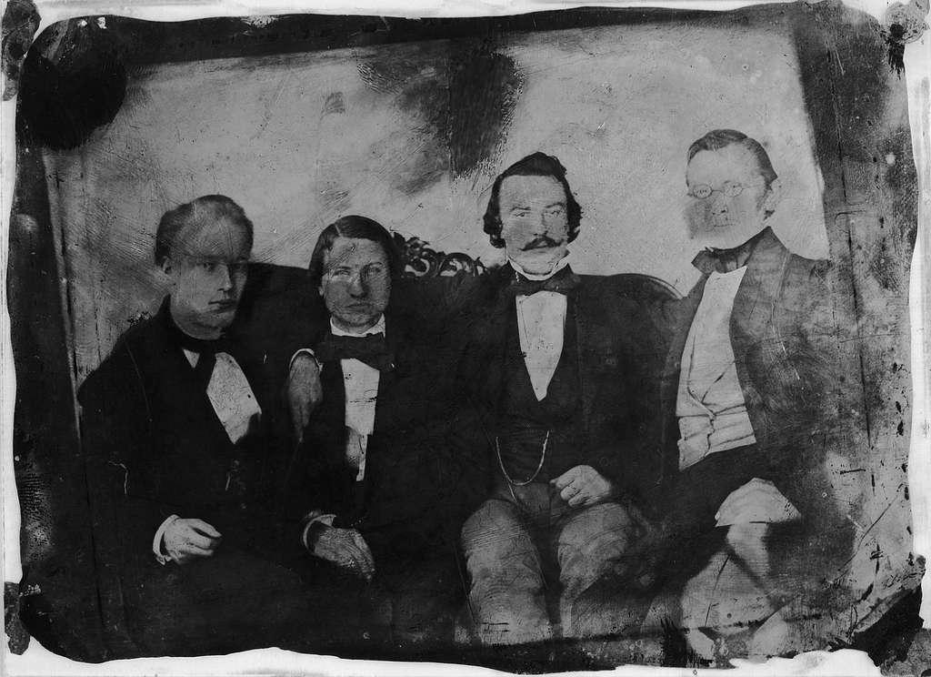 """Ambrotyp, fotografi, porträtt, på glas med kollodiumhinna.Bilden föreställer från höger Bokhandlare Lundström (Akademiska Bokhandeln i Uppsala), Bokförläggare W. Schultz, Uppsala samt 2 biträden hos Bonniers i """"basaren"""" på Norrbro, Stockholm.Fotografiet taget före 1858."""