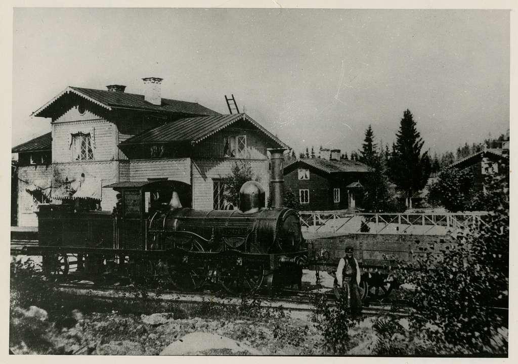 """Robertsholm station före namnbytet till Hofors. Framför stationshuset syns Gävle-Dala Järnvägs ånglok GDJ lok 4 """"Norden"""", samt stationskarl Olof Wallström, född 1836, död 26/6 1884. Anställd 1/5 1861."""