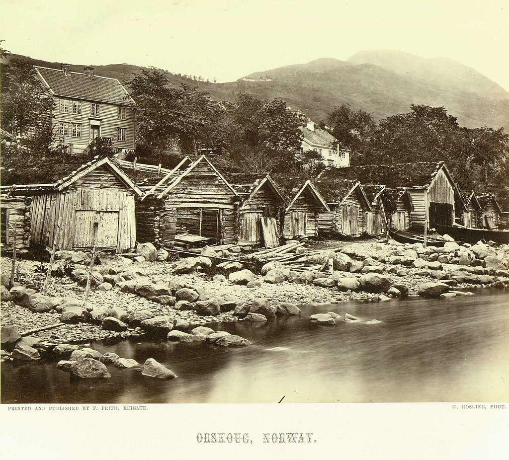 Landskap, Ørskog (tidligere Orskoug), Møre og Romsdal. Rekke med naust med bolighus i bakgrunnen.Fra serie norske landskapsfotografier tatt av den engelske fotografen Henry Rosling (1828-1911).