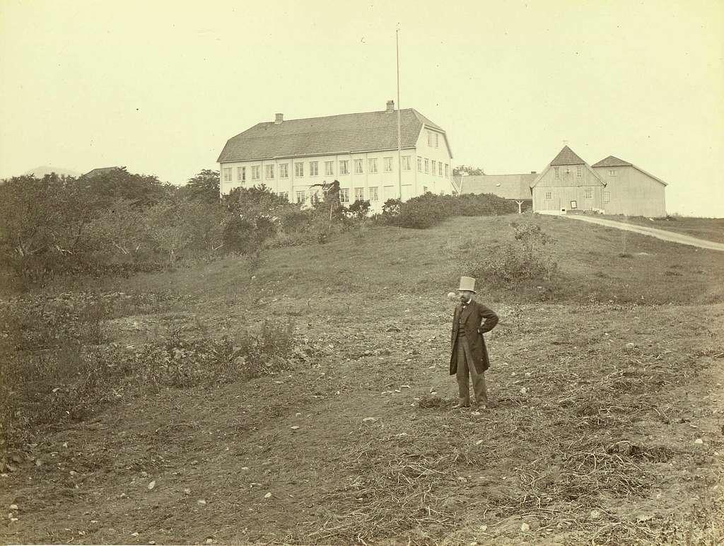Ris hovedgård i Oslo. Mann i flosshatt poserer foran stor hovedbygning med uthus omkring..Fra serie norske landskapsfotografier tatt av den engelske fotografen Henry Rosling (1828-1911).