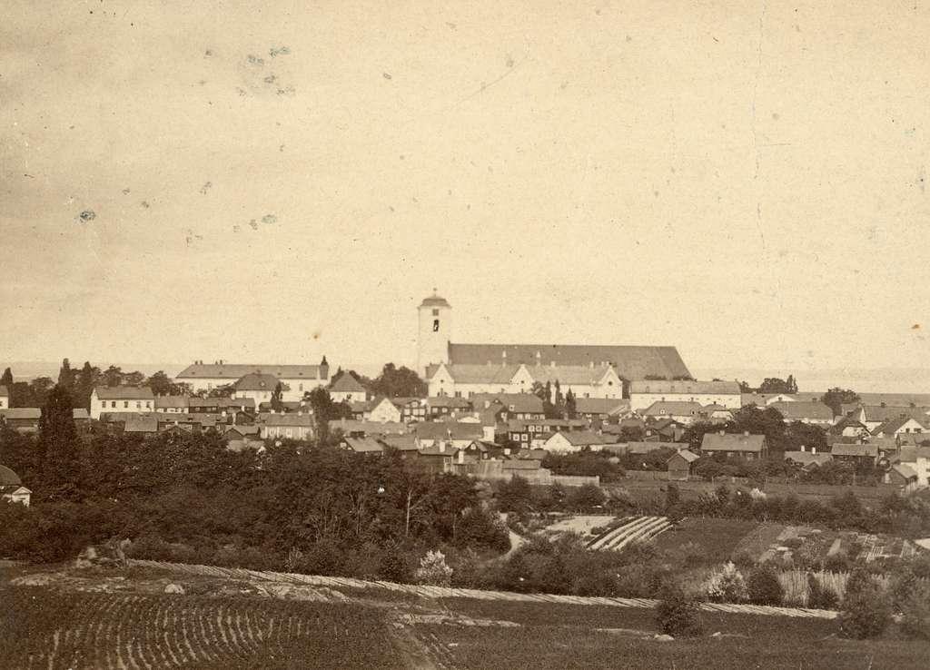 Vy mot Linköping sommaren 1864. Dominerande i bilden reser sig domkyrkan med sitt så kallade Hårlemanska torn som ersattes med nuvarande efter en omfattande ombyggnad från 1877. Framför kyrkan ses stadens läroverk, numera stadshus, som vid tiden var precis färdigställt. Övrig bebyggesle att nämna är slottet till vänster om kyrkan och det gamla gymnasiehuset till höger om läroverket. Den sistnämnda byggnaden fungerade från 1810 som logelokal för Linköpings frimurare.