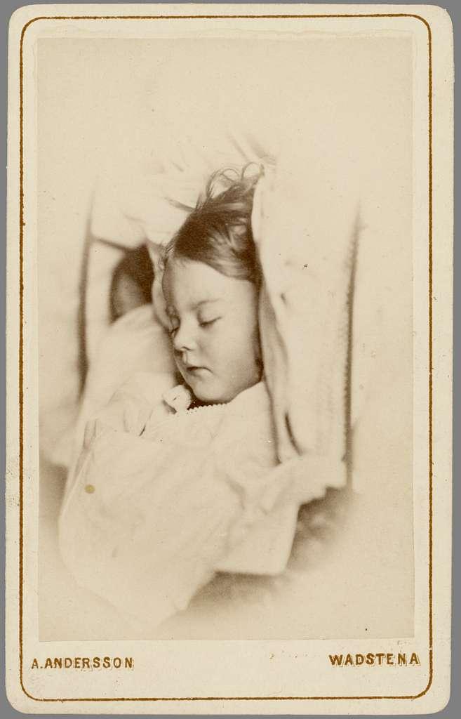Post mortem-porträtt av Esther Wallin. Dotter till lasarettsläkaren i Vadstena, Axel Wallin och hans hustru Amalia Wallin. Flickan var parets förstfödda barn, men lyckan bestod endast i 1 år, 10 månader och 26 dagar. Tyfusen släckte hennes liv den 17 februari 1874.