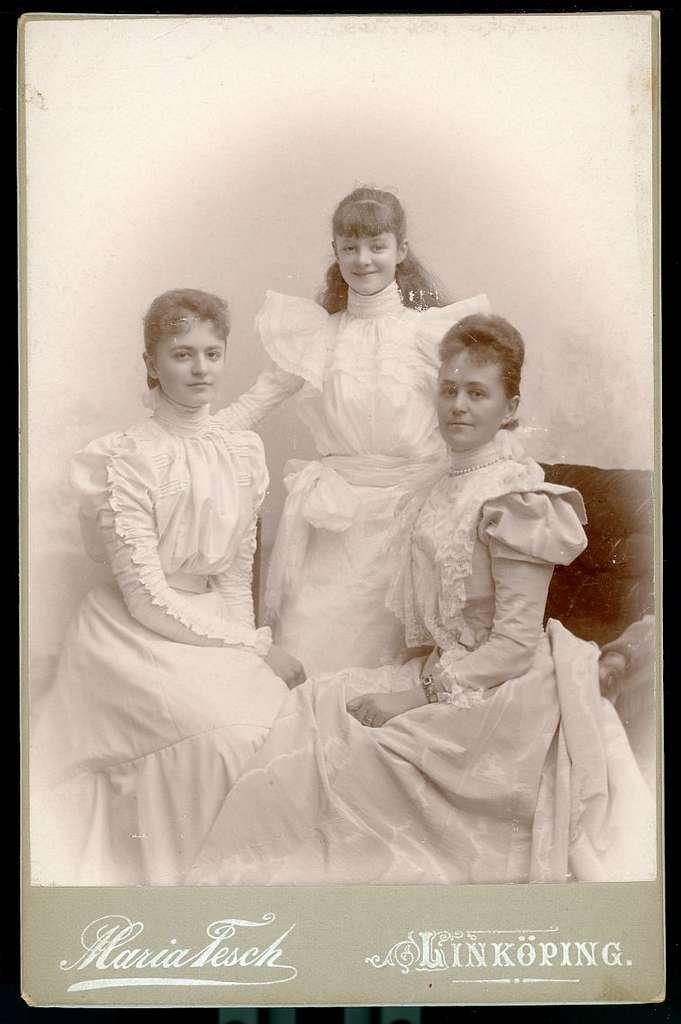 Kabinettsfotografi: tre kvinnor i olika åldrar i ljuss klänningar med krås på bröst, ärmar och puffärmar.
