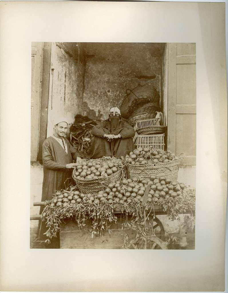 Vy över två personer som säljer apelsiner från en vagn.