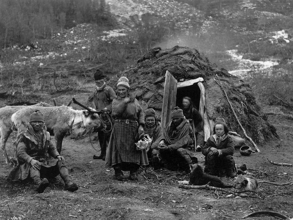 Svenske samer, muligens fra Karesuando, samlet foran en gamme. Antagelig Lyngen ca. 1885-1892.