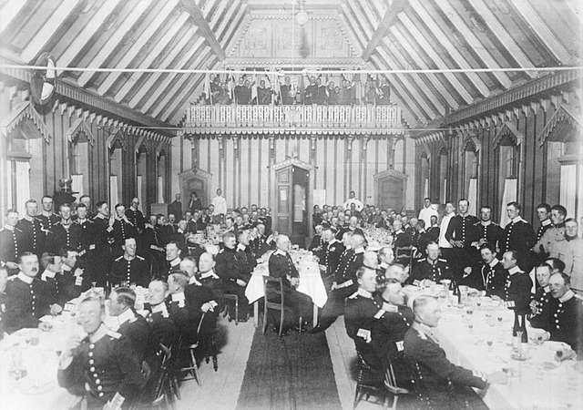 Måltid i officersmässen vid kung Oscar II:s besök på Malmen. Officerare sittandes vid långbord.