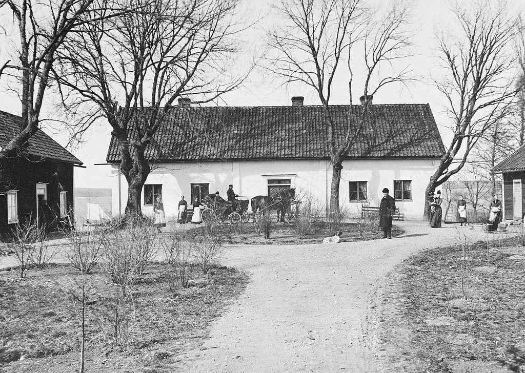 """Någon gång under 1870-talets första hälft förevigade den danskättade fotografen Peder Anton Eriksén denna vy mot Ekebyborna kyrkoherdeboställe. Vackert belägen på en udde vid sjön Boren. Ursprungligen uppförd 1735 och länge ansedd som en av de """"vackraste och bästa"""" i Aska kontrakt. Långt senare var bygganden dock i dåligt skick och 1928 byggdes ny prästgård närmare kyrkan. Året därpå skänktes den gamla prästgården till Nordiska museet för att flyttas till Skansen som prästgård till Seglora kyrka. Planen blev emellertid inte av utan huset blev kvar på ursprunglig plats och hyrdes ut. År 1989 skänkte Nordiska museet prästgården till Ask-Ekebyborna hembygdsförening. Samtidigt förklarades den som statligt byggnadsminne. Vid tiden för bilden disponerades bostället av kyrkoherde Per Dahlgren med familj. Det är honom vi ser intill rundeln till höger, rimligtvis vid sidan av maka, barn och tjänstefolk."""