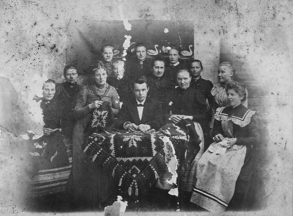 Gruppeportrett av 12 kvinner og 1 mann. De fire kvinnene i forrerste rekke sitter  sitter med sytøy i fanget