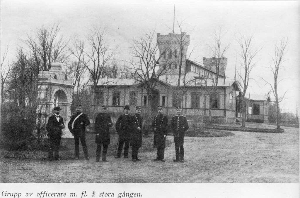 En grupp av officerare och andra män poserar framför officerssalongen på Malmen. Avfotografering av bild ur tryck.
