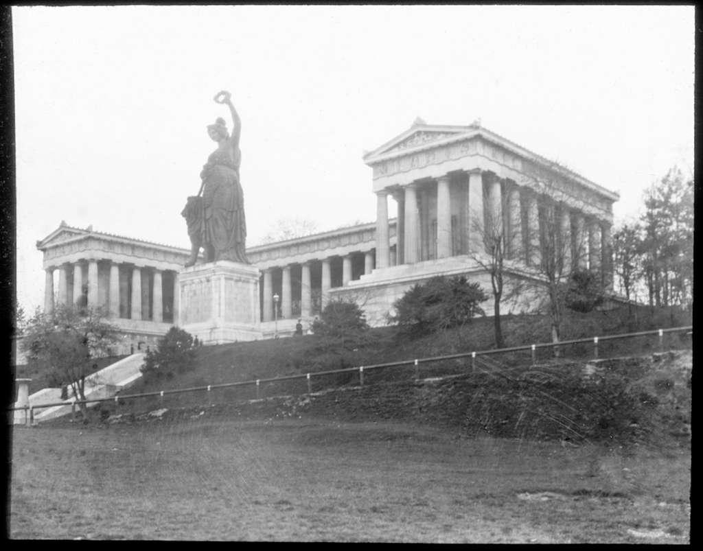 Skioptikonbild från institutionen för fotografi vid Kungliga Tekniska Högskolan. Motiv föreställande monumental byggnad med skulptur framför föreställande en kvinnogestalt som håller en lagerkrans i handen och med ett lejon vid sin sida. Bilden är troligen tagen av John Hertzberg under en resa i Europa.