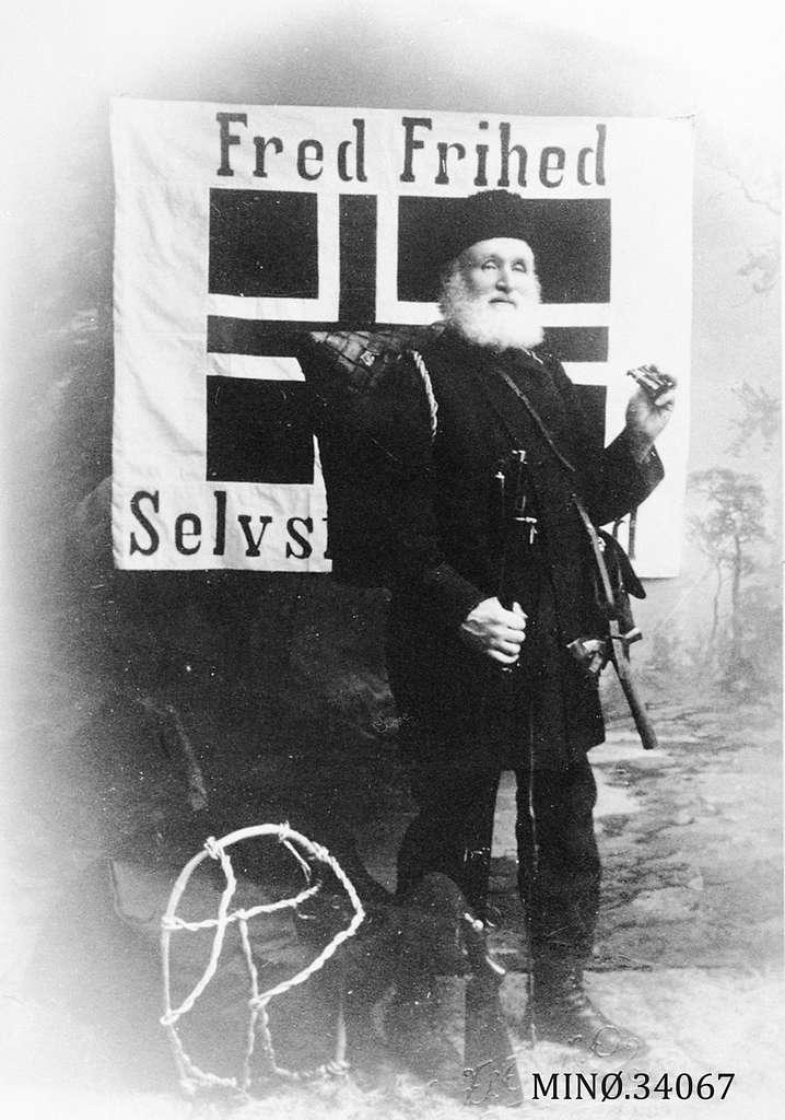 """Mann foran banner hvor det står """"Fred, Frihed og Selvstendighed"""""""