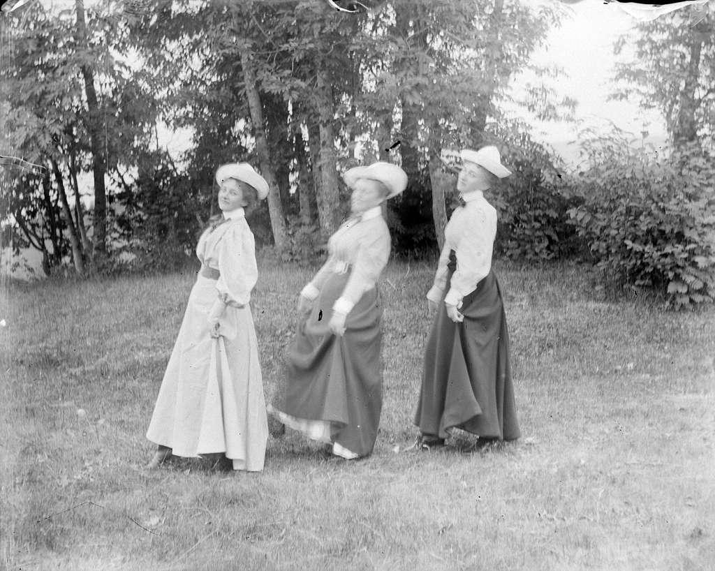 Tre kvinner med hvite hatter i en hage. Lol Misen (f. Mellbye) t. v.