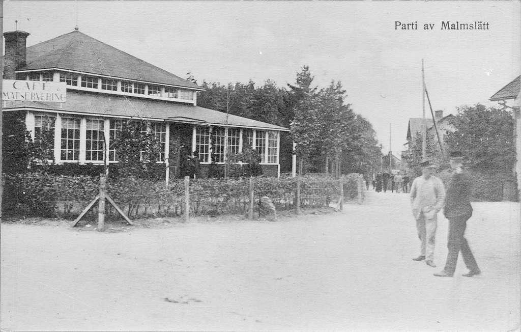 Byggnad i Malmslätts samhälle ca 1910. Café och matservering. Militärer i rörelse. Avfotografering av vykort.