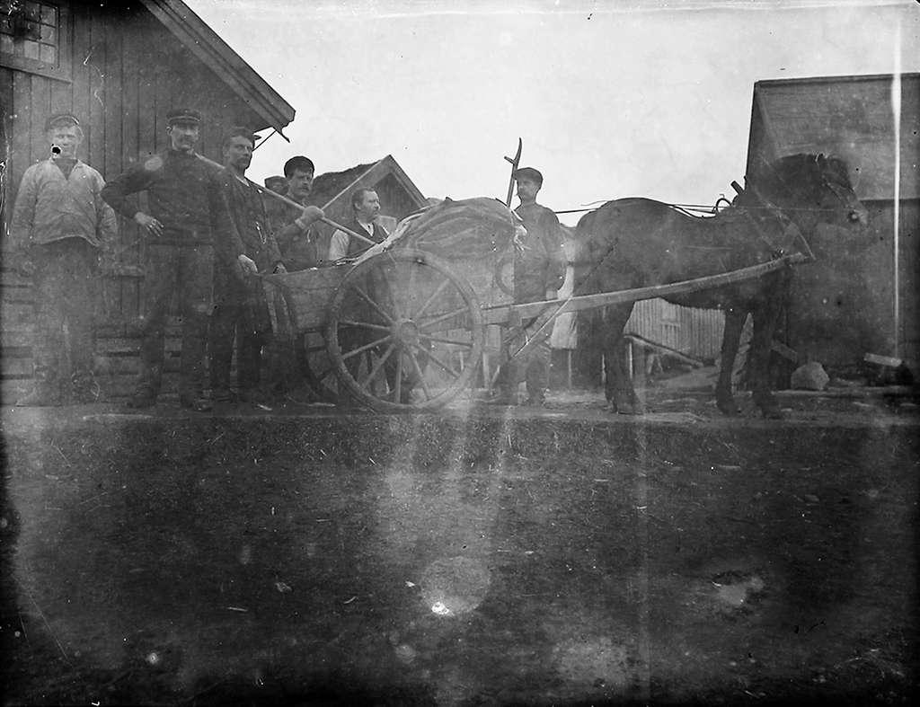 Gruppebilde. 6 menn med hest og vogn.Det ligger fisk i vogna.1 mann med uniformslue. Oppsynsmann? Hus i bakgrunnen.Bildet er muligens tatt i Lofoten.