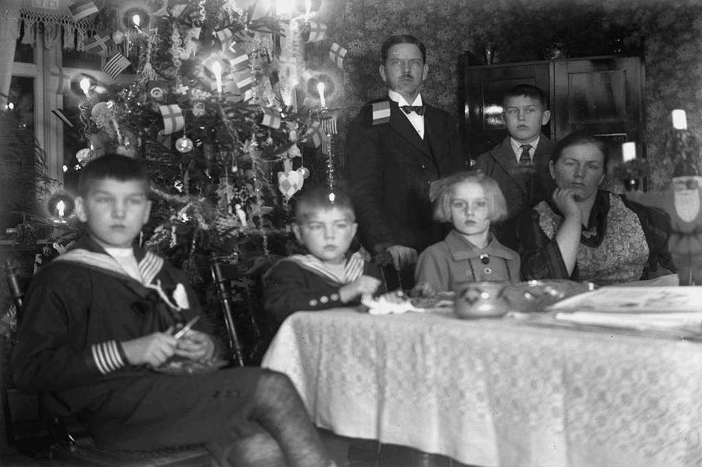 Rumsinteriör, julbild med julgran. Familjen Andersson. Sittande från vänster: Olof, Anders, Britta, Edit. Stående bakom dem fadern Erik Herman och Lars.