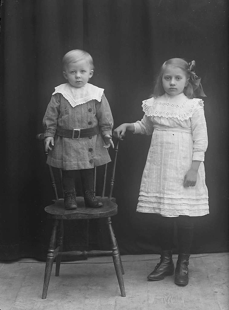 Portrett. En liten gutt og en pike. Gutten står på en pinnestol. Han har på seg mellommørk drakt med mørk belte, og piken står ved siden av stolen og lener høyrehånden sin på skulderbrettet. Hun er hvitkledt, og har hårsløyfe.Bildet er tatt på Reine i Lofoten.