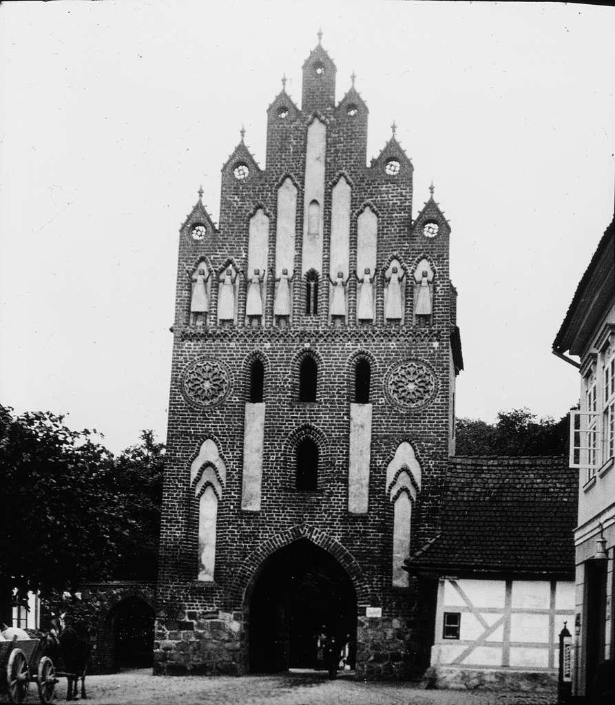 """Skioptikonbild med motiv av Neue Tor, port i stadsmuren, Neubrandenburg.Bilden har förvarats i kartong märkt: Resan 1912. Neubrandenburg 7. Text på bild: """"None Tor""""."""