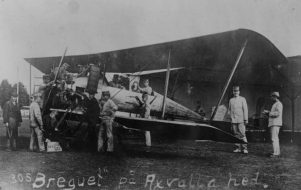 Underhållsarbete av flygplan B 1 Bréguet C.U 1 på Axevalla hed, 1912.  Vid noshjulet sitter Allan Jungner. Vid flygplansstjärten står Henrik Hamilton.