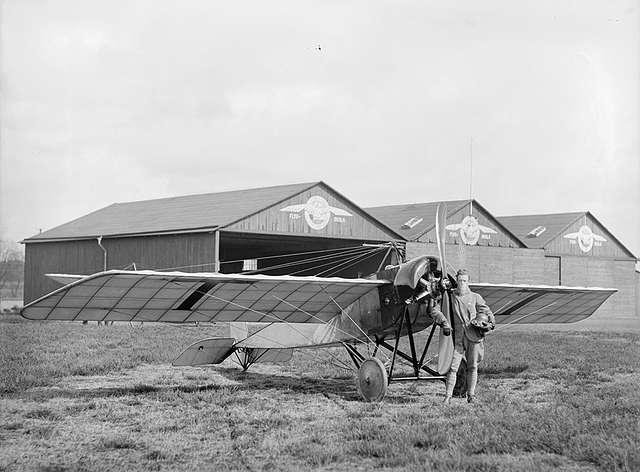 Flygare framför flygplan Thulin B uppställt framför hangarer i Ljungbyhed.