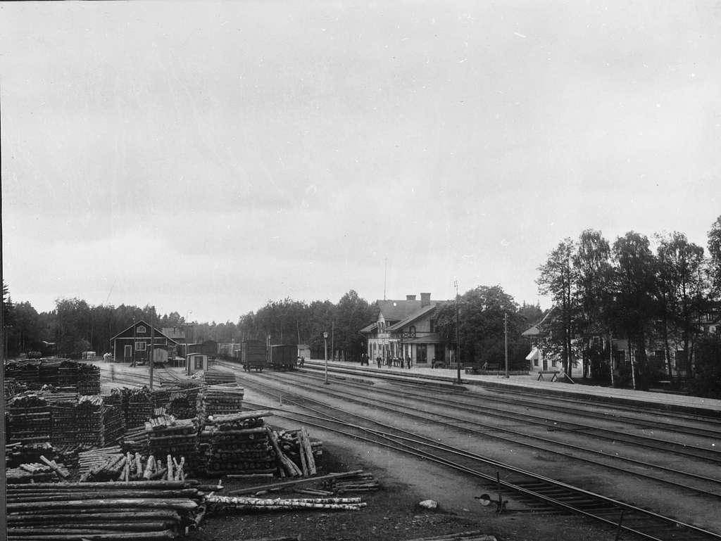 Bangård och stationshus vid Emmaboda järnvägsstation. Personalen står på perrongen. Godsmagasinet till vänster.