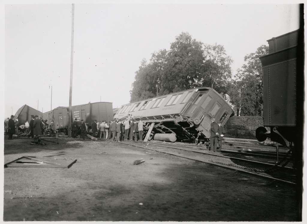 Vagnar och folksamling vid olycksplats på bangård.