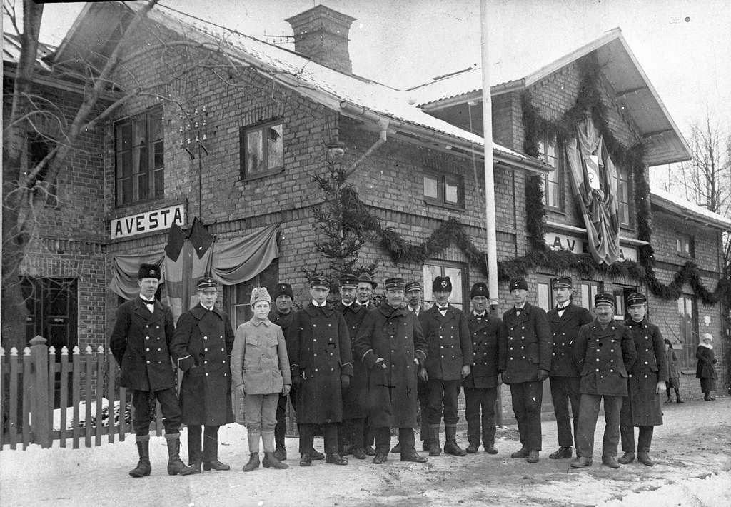 Personal framför Avesta station. Stationen dekorerad för statsinvigningen. Stationföreståndare Wictor Roslund stående längst fram i mitten.