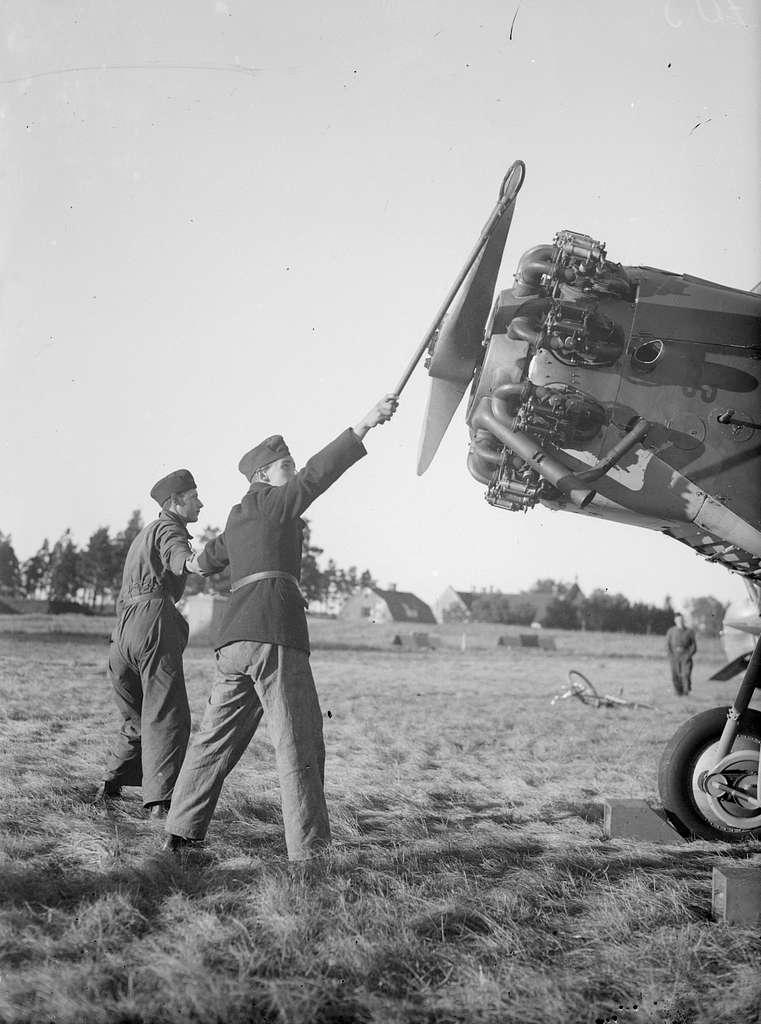 Start av flygplansmotor med hjälp av stropp. Två militärer vid flygplanspropeller.
