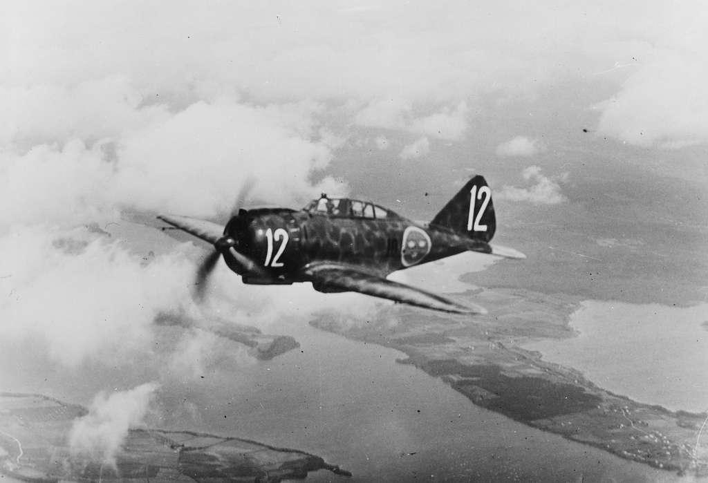 Flygplan J 20 märkt nummer 12 ur F 10 Ängelholm flyger över fält.
