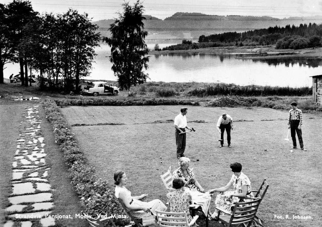 Strandvik pensjonat, Korgerstuvika, Moelv. Gruppe menn spiller krokket på plen. Gruppe damer drikker kaffe. Mjøsa i bakgrunn.