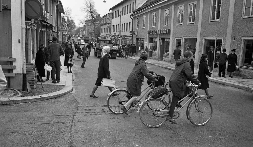 Folkliv på Nygatan. Cyklister, lastbilar och bilar. Människor som går på trottoarer och över gatan.På vänster sida ses skylten till Marks varuhus och Bröd-skylten. På höger sida ligger en bar, EPA, en tobaksaffär och Nils Adamssons.