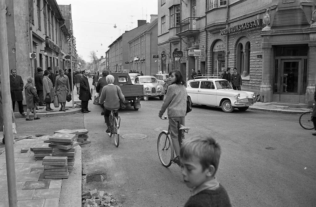 Trafik på Nygatan. Många bilar, människor som promenerar, en cyklist. Till vänster ses Öhrman & Melander, Järnaffären och hotellet. På höger sida ligger Olssons, Nilssons skor, Modemagasinet och Jordbrukskassan.I förgrunden ligger stenplattor. Trottoaren har gjorts iordning.