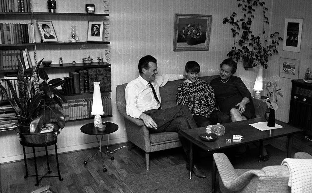 Brudpar 1946 (hemma hos), 9 mars 1966En familj bestående av en far, en mor och deras unge tonårsson sitter i en soffa i ett vardagsrum. På väggarna hänger tavlor. En bokhylla syns till vänster. Framför familjen i soffan står ett bord.