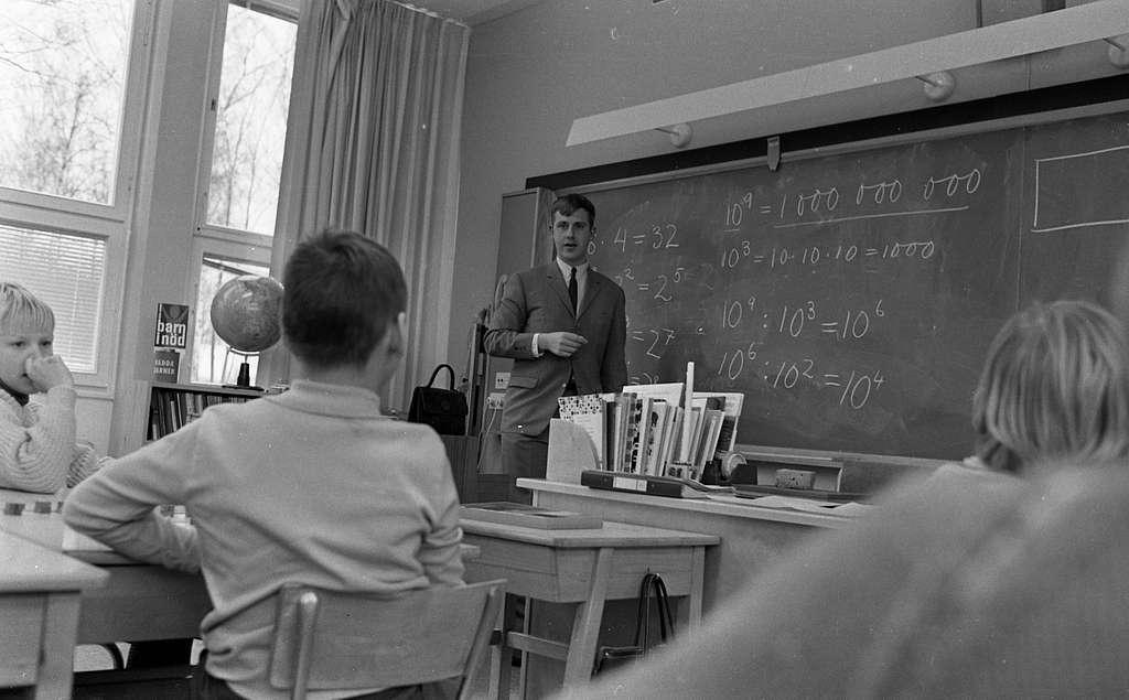 Matte Expr. i Norrbyskolan 8 december 1967Elever sitter i skolbänkar i ett klassrum på Norrbyskolan under en matematiklektion. En manlig lärare klädd i ljus kostym, vit skjorta och svart slips står framme vid svarta tavlan. På den har han skrivit en massa tal och matematiska beräkningar. En kateder står bredvid honom.                                                                                                                                                                                                                                                                                                                                                                                                                                                                                                                                                                                                                                                                                                                                                                                                                                                                                                                                                                                                                                                                                                                                                                                                                                                                                                                                                                                                                                                                                                                                                                                                                                                                                                                                                 