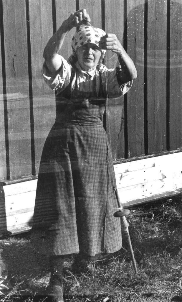 Bø, Telemark 1940. Anne Østbø spinner med gamme håndtein fra Ruddal.