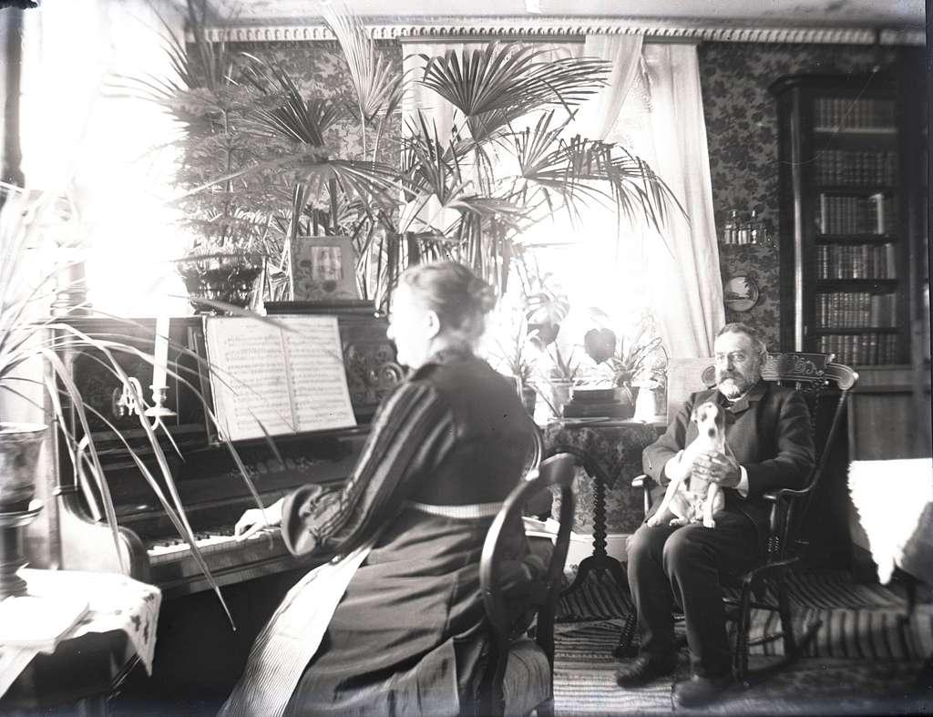 En äldre kvinna som spelar piano och en äldre man med en hund i knät.
