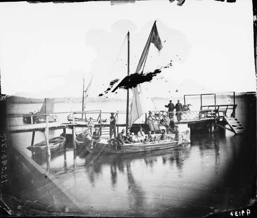Sällskap på mindre segelbåt i hamn.