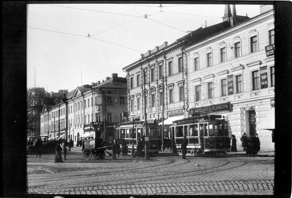 Vy över torget vid Södra kajen - Norra Esplanadgatan i Helsingfors. Helsingin Kaupungin Liikennelaitos, HKL spårvagn 46 och 37 ses mitt i bild, till vänster om vagnarna ses en hästtransport.