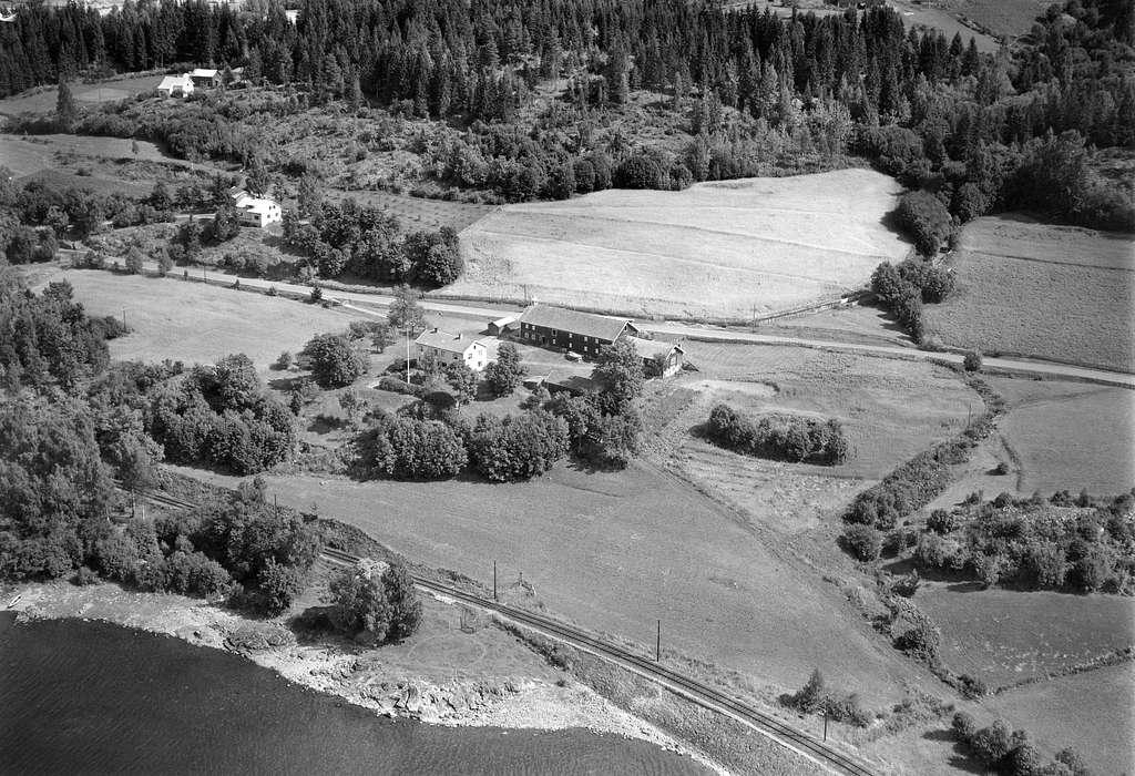 NEDRE MOSTUE (MORSTU) GÅRD, STRANDLYKKJA, Flyfoto av den gamle gjestgiver og skysstasjonsgården. Låven ble revet i 1957 for å gi plass til utvidelse av riksveg 50 som ble anlagt forbi her ca. 1963-65. Fra nederste høyre hjørnet og på skrå oppover til gårdstunet gikk den gamle Kongevegen. Gården er nå revet i forbindelse med anleggelse av ny E6 og jernbane.